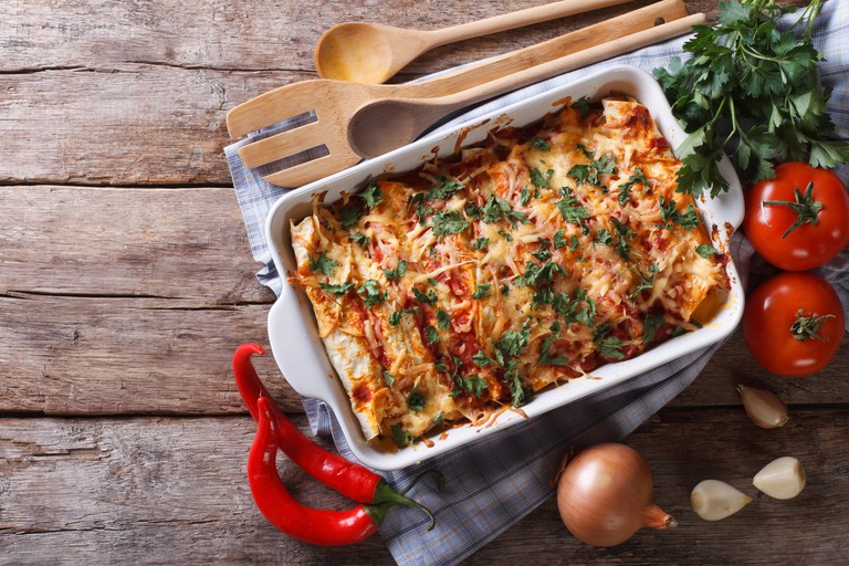 Mexican enchilada in a baking dish with the ingredients on the table. horizontal view from above