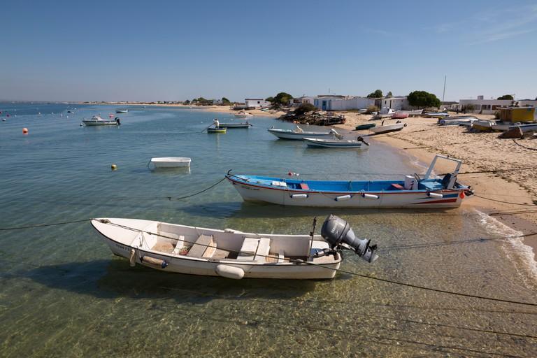 Boats moored off beach of Ilha do Farol, Culatra barrier island, Olhao, Algarve, Portugal, Europe