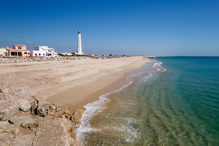 Lighthouse and beach of Ilha do Farol, Culatra barrier island, Olhao, Algarve, Portugal