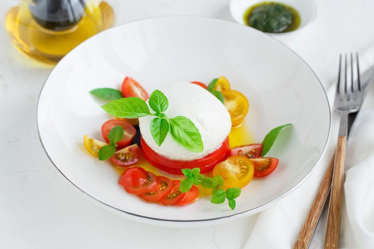 Caprese salad with red and yellow tomatoes, mozarella, basil and olive oil. Close view. White background