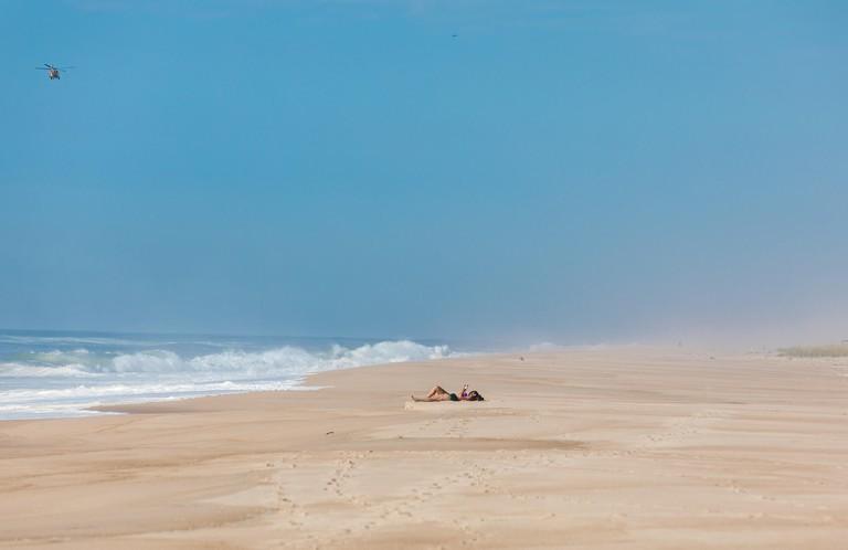 KJACWJ single woman reading a book in the sun on an ocean beach in east hampton, ny