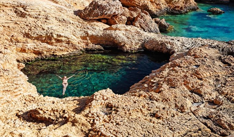 KMFBN3 Young woman swim in the natural swimming pool Pissina of Koufonissi island, Greece