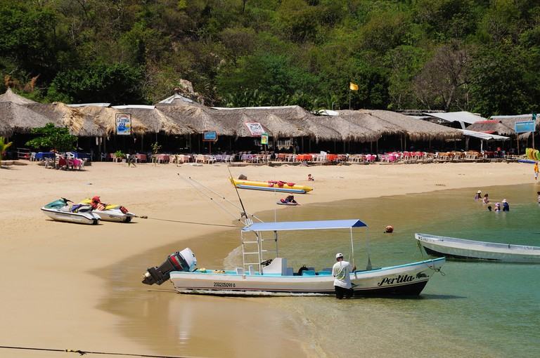 Mexico, Oaxaca, Huatulco, Tour boats and beach side restaurants on sandy Playa La Entrega beach.