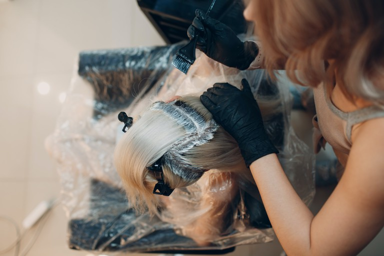 Young woman hairdresser dying hair at beauty salon. Professional hair roots coloring. maksim-chernishev-PaEFID0r2yo-unsplash