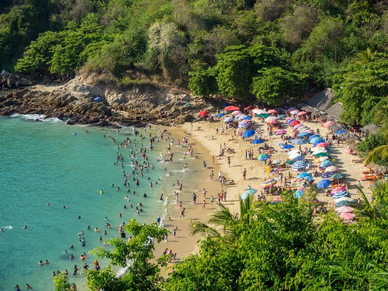 Puerto Escondido, Oaxaca, Mexico, South America: [Playa Carrizalillo, crowdwed natural beach, tourist destination]