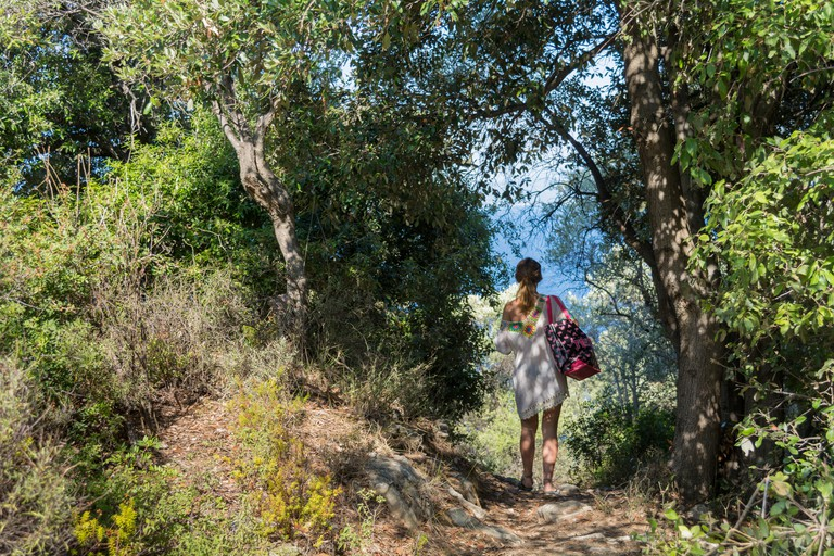 MHJBRE girl walking in a mediterranean forest in skiathos
