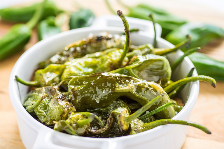 Fried Green Padron Peppers in White Bowl. Pimientos de Padron.