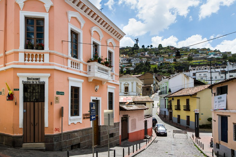 QUITO, ECUADOR - OCTOBER 27, 2015: A typical street scene in the colourful La Ronda area of historic Quito, Ecuador with the famous winged Virgin Mary