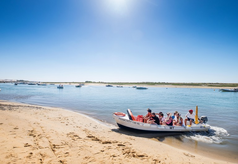 Tourists cross the water at the Ria Formosa from Cabanas Village to Cabanas Beach at Cabanas in the Algarve, Portugal
