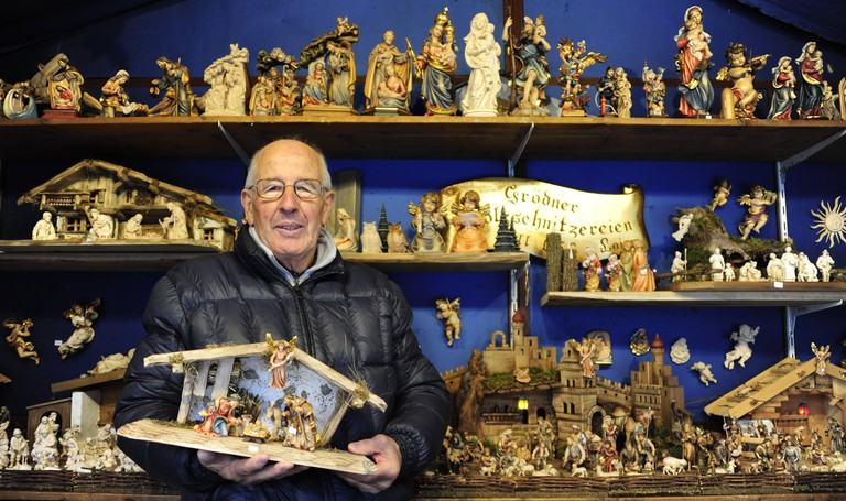 Dealer Franz Fill from South Tyrol at his stand with crib figures at the Christmas market on Weissenburger Platz.