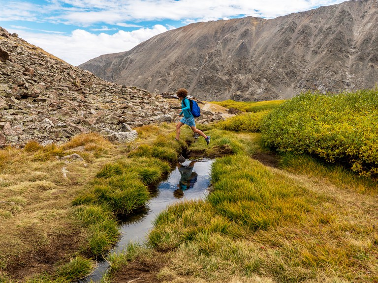 R48MGG Woman jumps across creek along the Blue Lakes Monte Cristo Gulch trail, Rocky Mountains near Breckenridge, Colorado