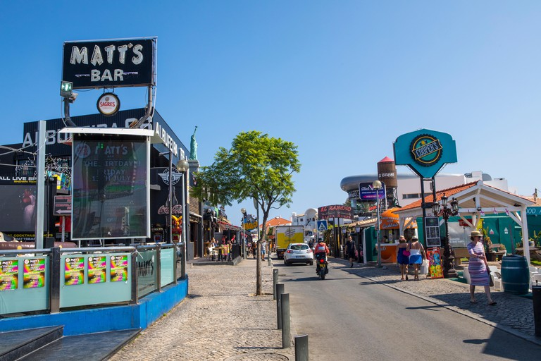 ALBUFEIRA, PORTUGAL - JULY 13TH 2018: A view of Avenida Sa Carneiro, known as The Strip, in Albufeira, Portugal on 13th July 2018.  The Strip is known