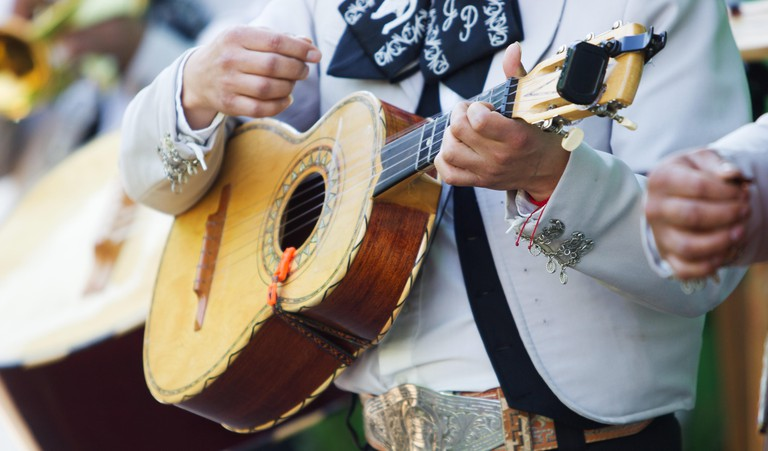 Mexican mariachi with white traditional costumes playing the vihuela at a party