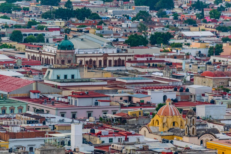 Partial view of Oaxaca city center, from above, with many colorful buildings and dome rooftops, in Oaxaca, Mexico