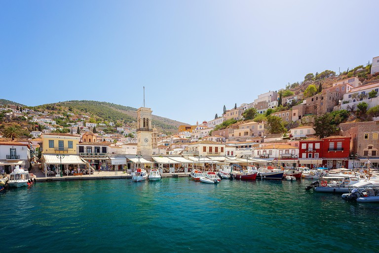 Hydra, Greece - June 2, 2018: Beautiful harbor with cycladic architecture hillside town behind, on the Greek Island of Hydra. Central Clock tower in H