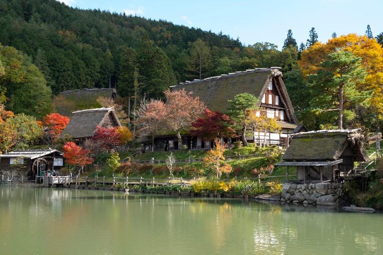 T810B7 Autumn foliage and traditonal thatched buildings around a lake at Hida Folk Village, Hida No Sato, Takayama, Honshu, Japan, Asia