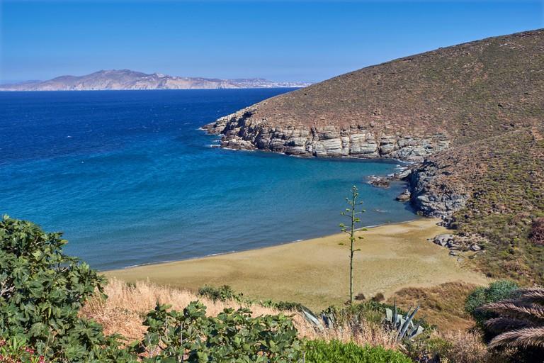 Pachia Ammos Beach near Agios Ioannis Porto with Mykonos in the distance. Tinos, Greece.