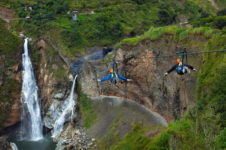 Tourists Zip Lining Like Birds Over The Rio Pastaza Valley, River Gorge,Toward The Agoyan Waterfalls, Tallest Waterfall of The Ecuadorian Andes, Route of The Waterfalls, Ruta de las Cascadas, Banos, Gateway To The Amazon, Tungurahua Province, Ecuador