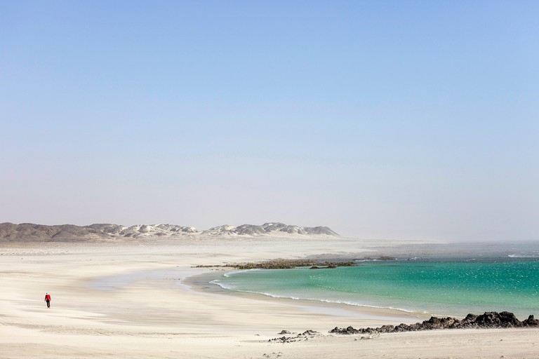 Man walking on beautiful beach on Masirah Island in windy conditions, Oman, Middle East
