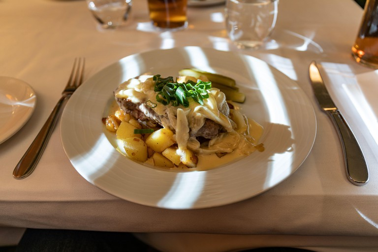 Sirloin steak with creamed onions and pan-fried potatoes on a restaurant table