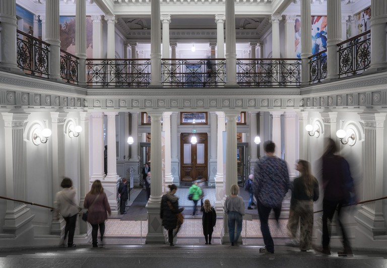 People walk down a steps leading a grand-looking doorway