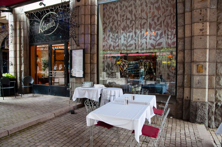 Dining tables on a street outside of a restaurant called Kosmos