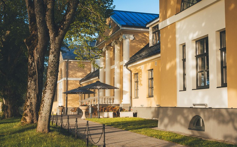 The classical-style exterior of Skrunda Manor with tall columns on a tree-lined street