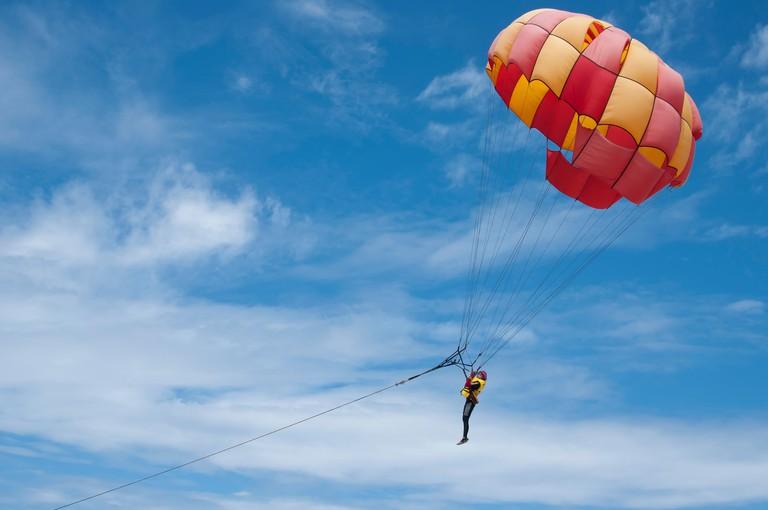 A paraglider floats over Dreamland Beach, Bali