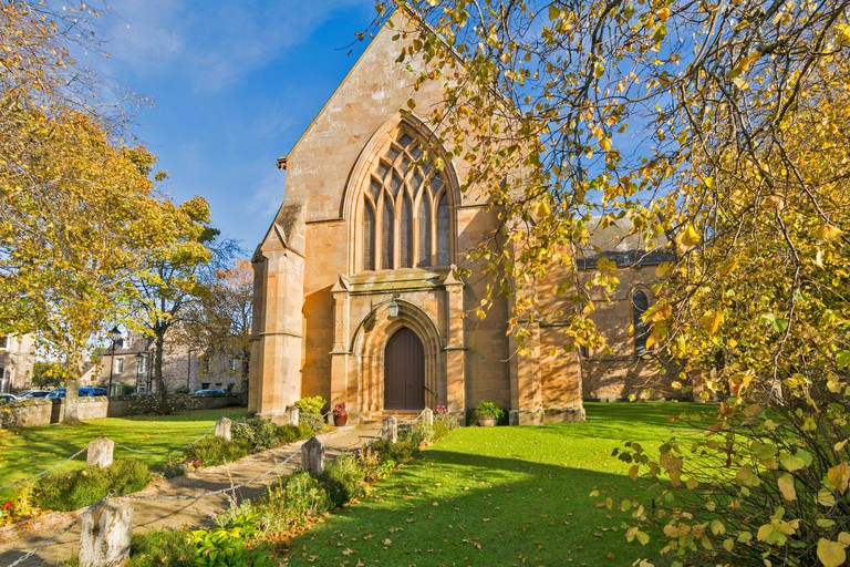 DORNOCH CATHEDRAL SUTHERLAND SCOTLAND FOOTPATH TO DOOR AND SURROUNDED BY AUTUMNAL TREES