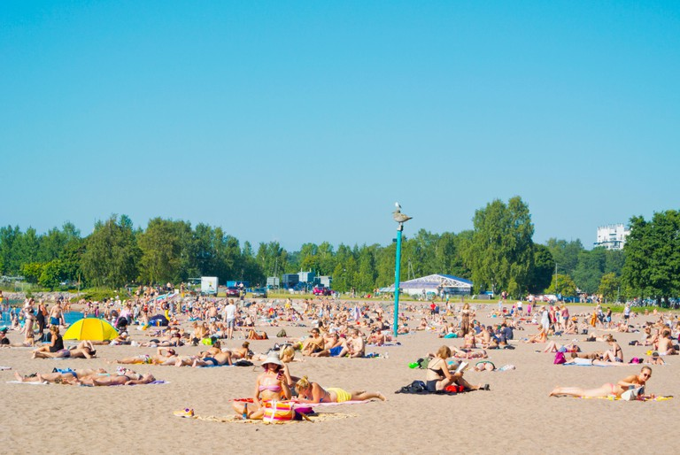 Multiple tourists sunbathe on a beach, with greenery and some building in the background