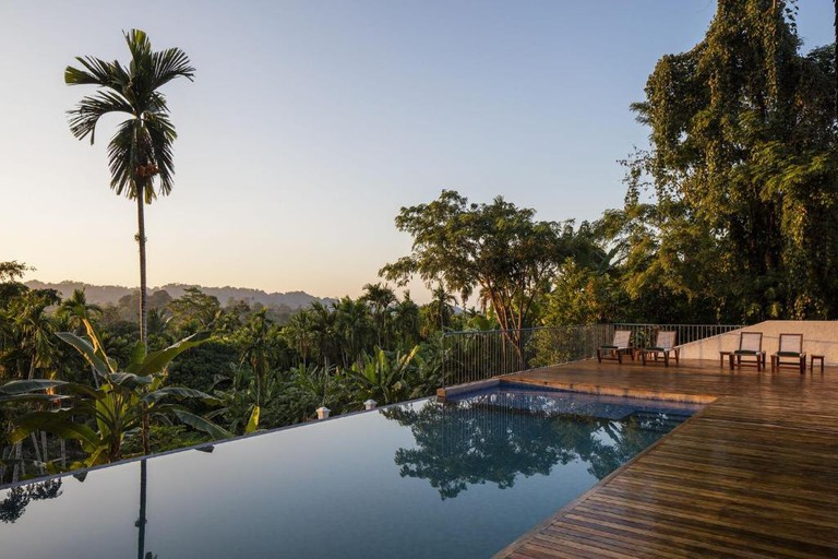 The wooden deck and infinity pool, looking out over palm trees and forest, at Jalakara