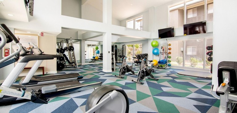 Home gym with running machines and geometric carpet in Landing Modern Apartment With Amazing Amenities