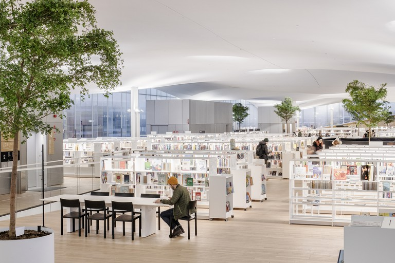A quiet library with white shelves and large glass walls in the background