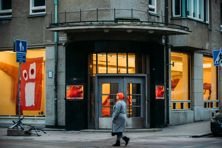 A woman walks past the entrance to an art gallery
