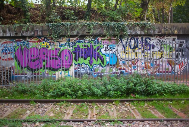 A wall of graffiti along the railroad tracks