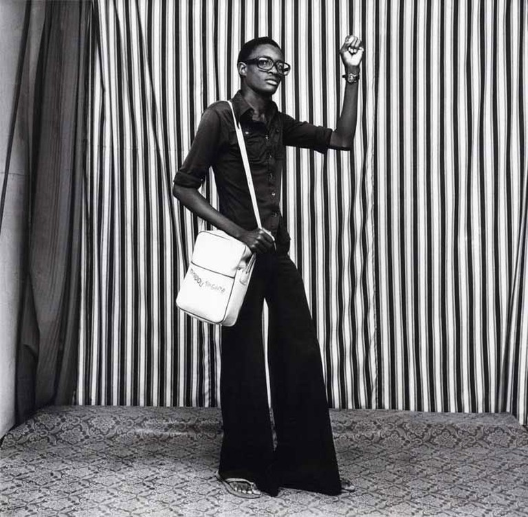"""Young man with bell bottoms, bag and watch."" By Malick Sidibé 