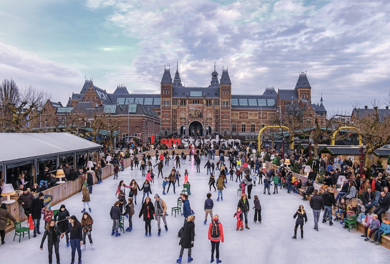 Ice skaters on the ice rink at the Museumplein, with the Rijksmuseum