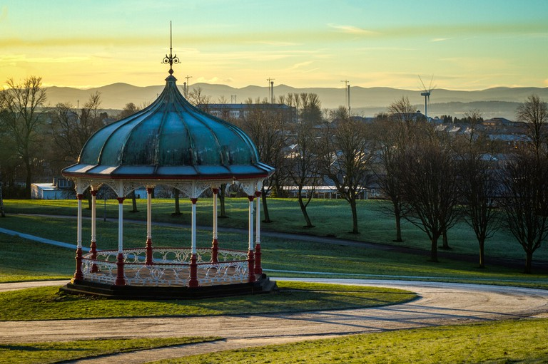 Bandstand in Dunfermline Park just after Sunrise with wind turbine and Queensferry Crossing towers in the distant background
