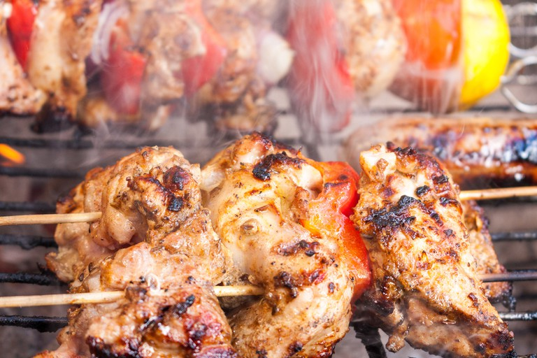 Chicken shawarma kebab skewer gently cooking on a smoking barbecue © Timages / Shutterstock