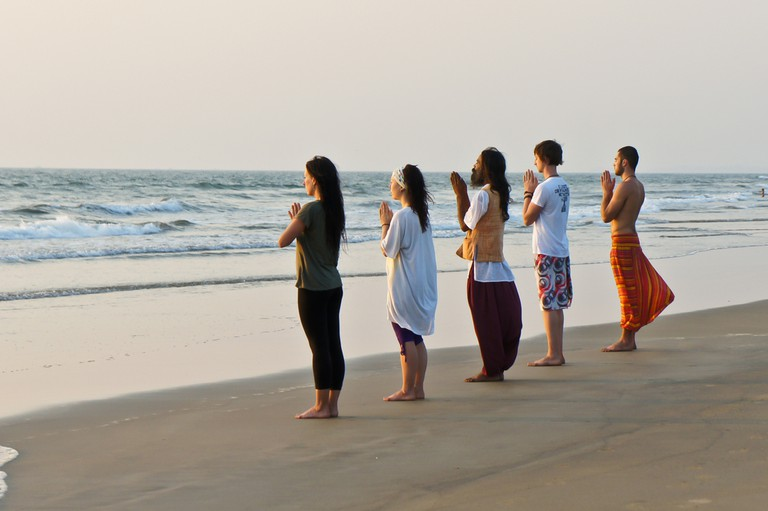 Indian yoga master and his international students meditate at sunset on the Goa beach, India