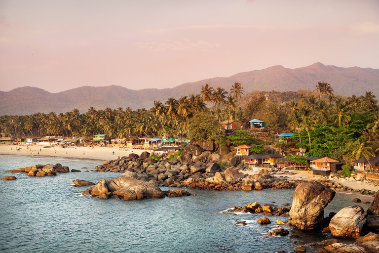 Beautiful view of tropical sunset beach with bungalow and coconut palm trees at Palolem in Goa, India