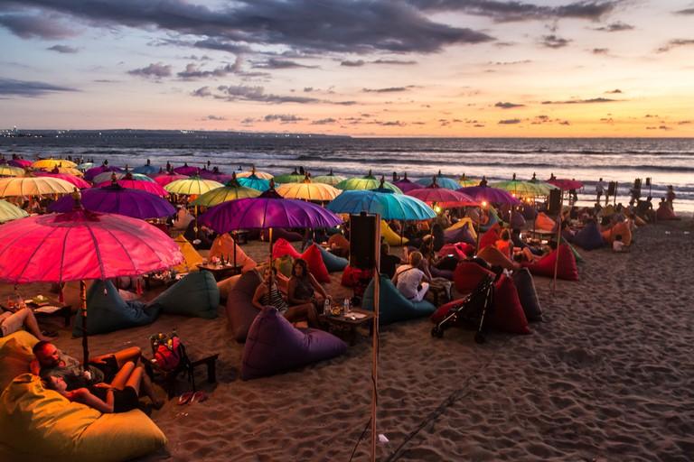 Tourists enjoy the sunset at a bar on Kuta beach in Seminyak, Bali