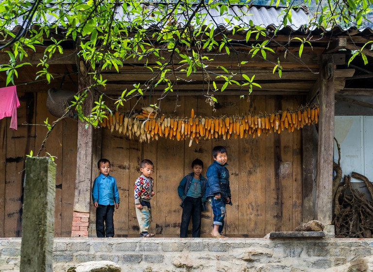 Children standing on the porch of a traditional wooden house.