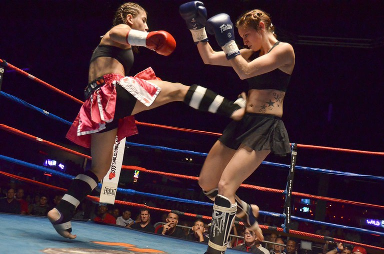 One fighter executes a Muay Thai teep kick against her opponent in a women's Muay Thai match. | © Eric Langley/WikiCommons