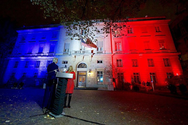 John Kerry looks on as U.S Embassy in Paris is lit up in the French tricolor after the terrorist attacks/©U.S department of State/WikiCommons.