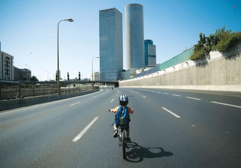 Boy riding his bike on the freeway on Yom Kippur