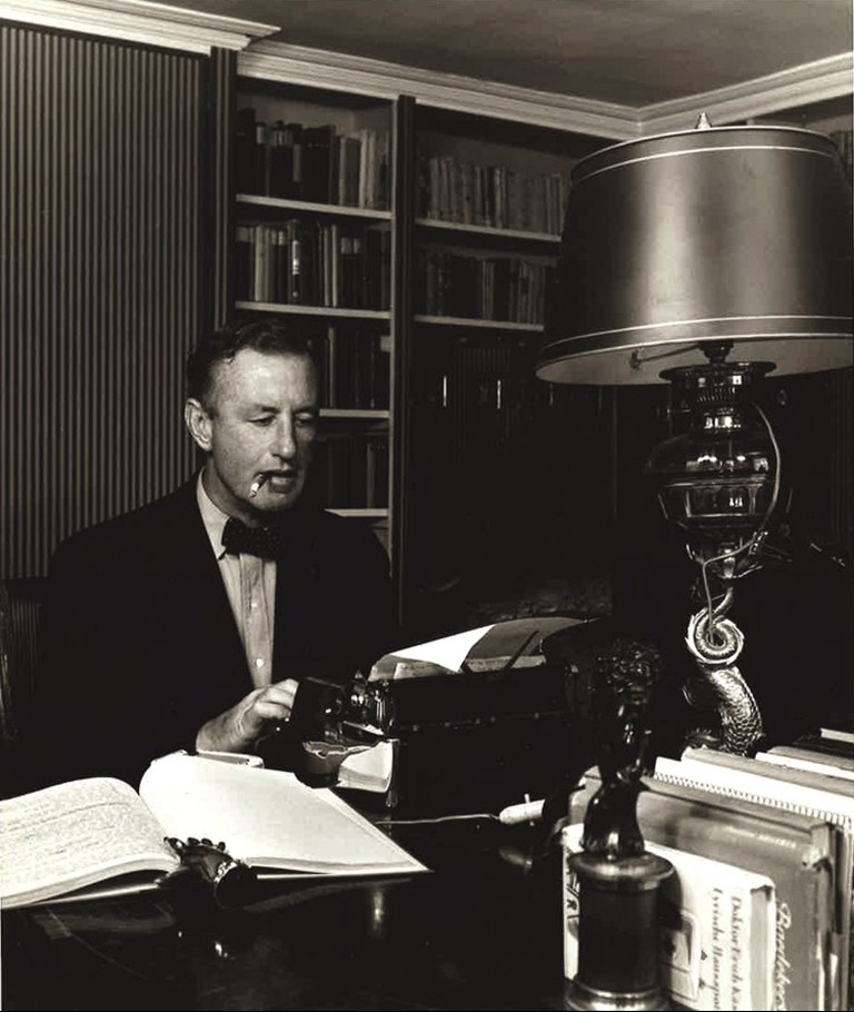 Ian Fleming at work on his golden typewriter | © The Ian Fleming Estate
