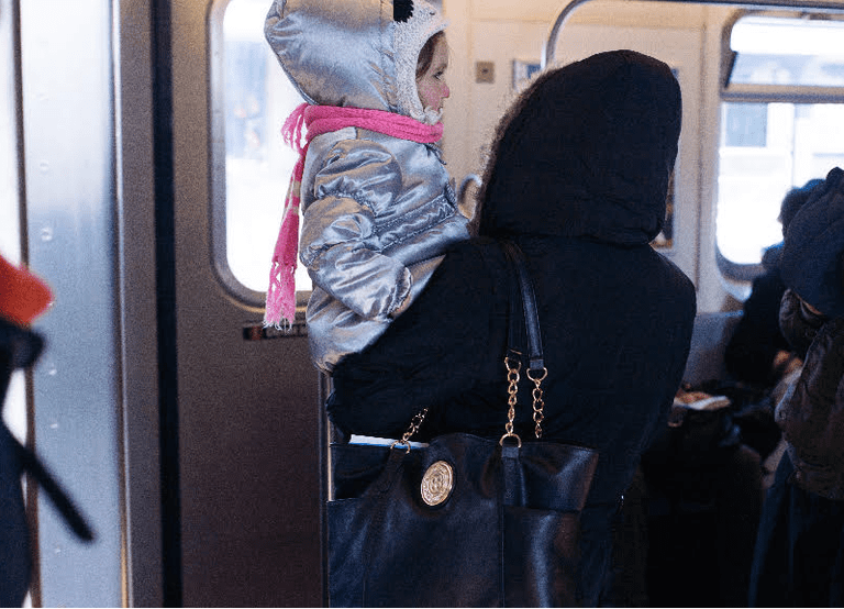 Mother holds daughter on the 7 train | © Smart Scott Photography