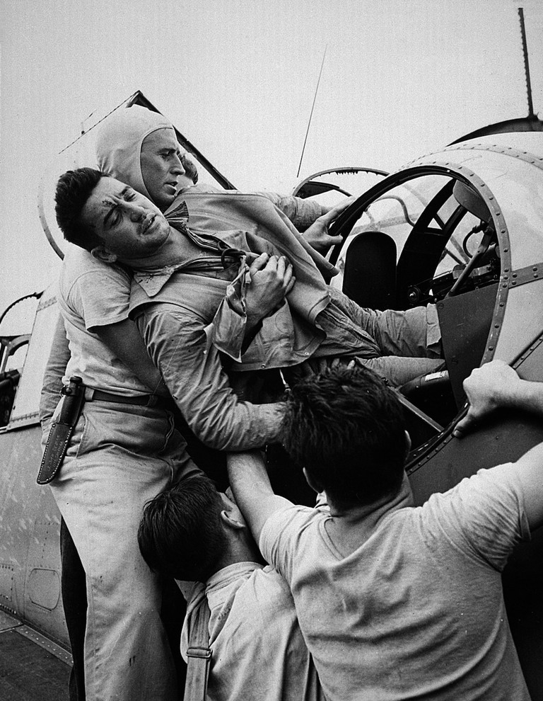 Crewmen aboard USS Saratoga lift AOM Kenneth Bratton, USNR, out of a TBF Avenger's rear turret after a raid on Rabaul on 5 November 1943 | © Lt. Wayne Miller/WikiCommons