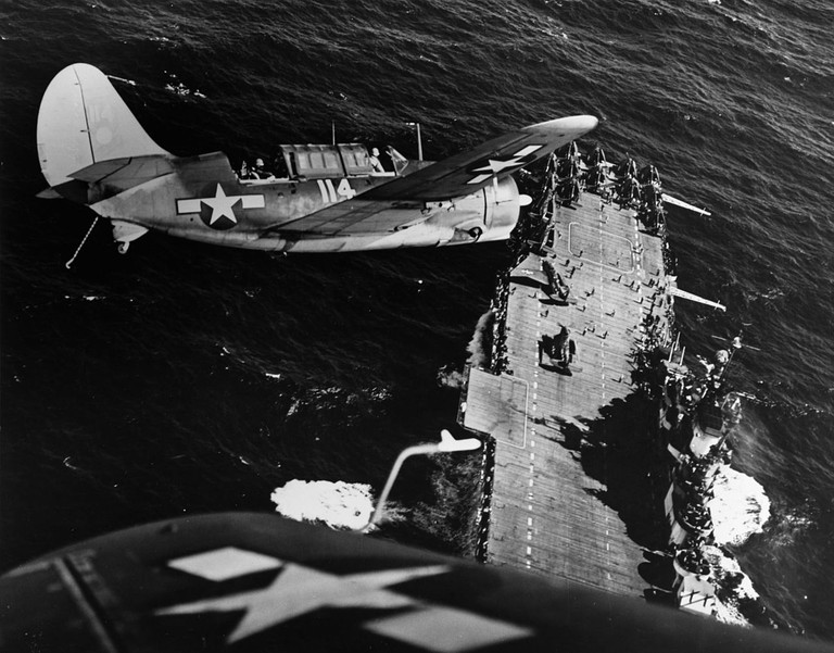 Two U.S. Navy Curtiss SB2C-3 Helldiver aircraft from Bombing Squadron 11 (VB-11) bank over the aircraft carrier USS Hornet (CV-12) before landing, following strikes on Japanese shipping in the China Sea, circa mid-January 1945 | © Lieutenant Commander Charles Kerlee, USNR/WikiCommons